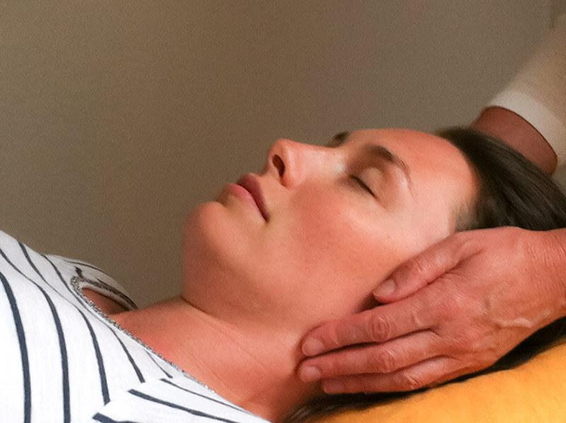 Reiki - Frau legt Hände an Kopf der Patientin